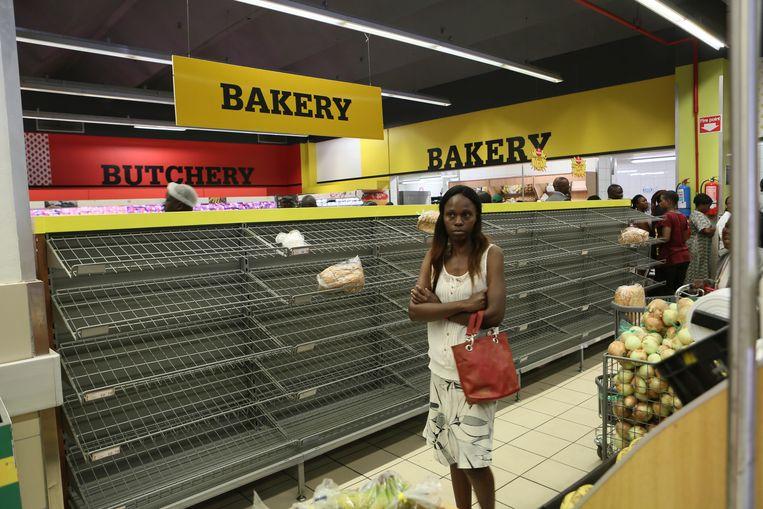 Lege schappen in een supermarkt in Harare, de hoofdstad van Zimbabwe.  Beeld AP