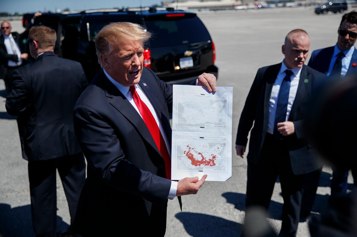 President Donald Trump laat op een kaart zien dat IS volledig uit Syrië is verdreven. De onderste kaart toont de gebieden die IS in november 2016 had veroverd. Op de bovenste kaart zijn geen rode gebieden meer te zien, wat volgens Trump betekent dat IS geen gebied meer bezit in Syrië.