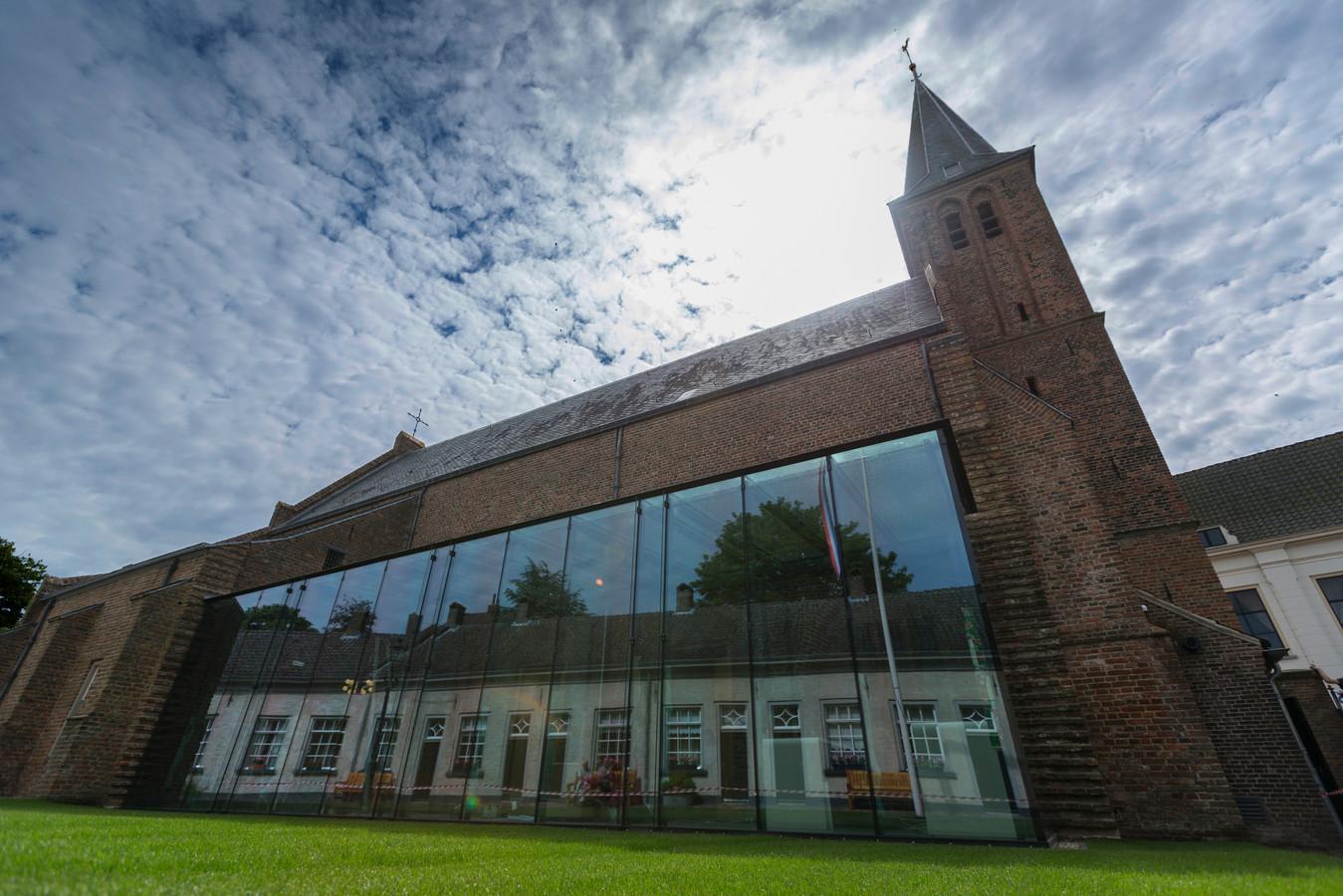 De glazen wand tegen de Gasthuiskerk weerspiegelt de monumentale huisjes van het Doesburgse Gasthuishofje.