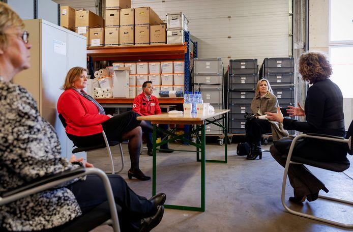 Op veilige afstand praat koningin Máxima met medewerkers van het Rode Kruis.
