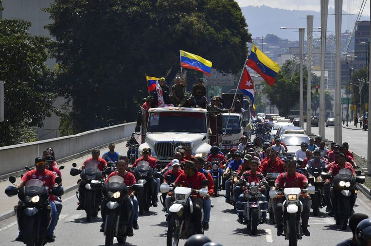 Supporters van Maduro vieren feest na zijn herverkiezing. De gemaskerde mannen zijn lid van La Piedrita, de knokploeg van het regime.  Beeld AFP