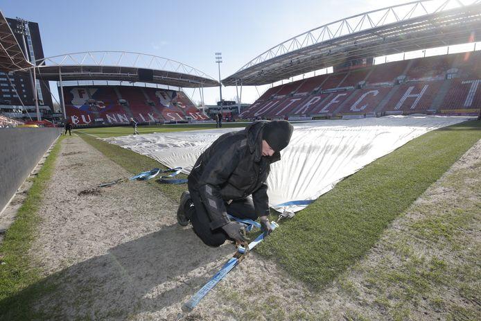 De grasmeester van stadion Galgenwaard treft voorbereidingen voor een tent over het grasveld van FC Utrecht.