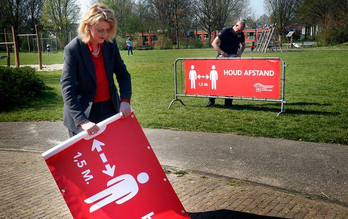 Burgemeester Reinie Melissant rolt in wijkpark 't Haagje een van de spandoeken uit. Bart de Bruijn van de gemeentelijke buitendienst bevestigt een doek aan een dranghek.