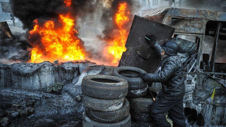 Een demonstrant beschermt zichzelf met een schild tijdens protesten tegen de regering. Beeld EPA