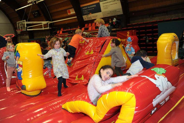 De kinderen leven zich uit op het reusachtige springkasteel in de sporthal.