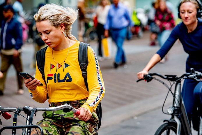 Een jonge vrouw gebruikt haar telefoon op de fiets