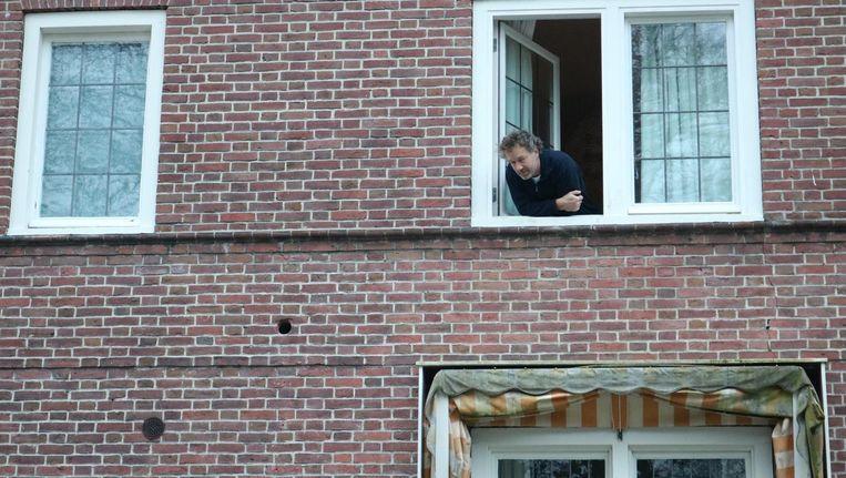 Sybren van Haga hangt uit het raam van zijn woning. Beeld ROOD