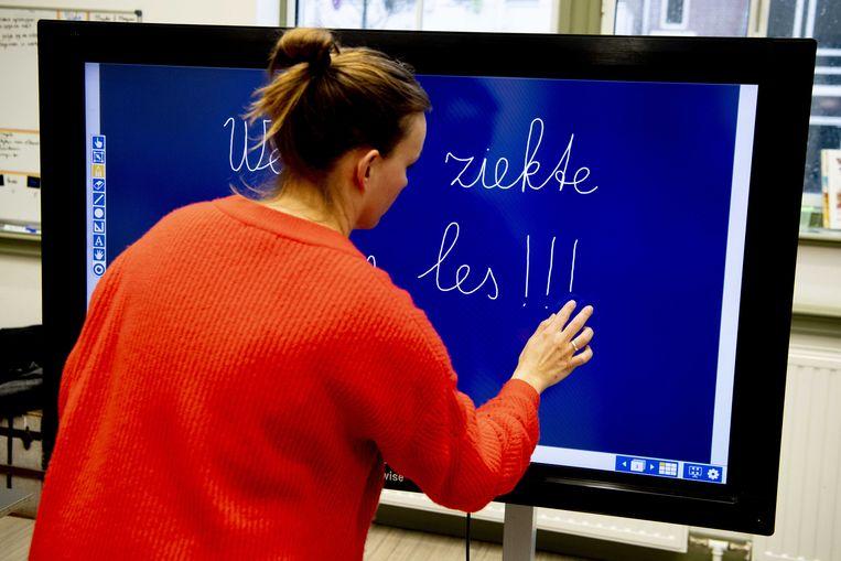 Een leerkracht schrijft op een digitaal schoolbord in een klas van een basisschool de tekst 'wegens ziekte geen les'. Het vervangen van zieke docenten wordt een steeds groter probleem door het lerarentekort, met name in de grote steden. Beeld ANP