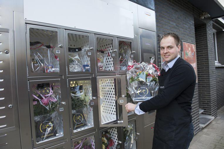 Zaakvoerder Dirk de Goede bij de bloemenautomaat langs de Bredabaan.