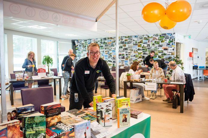 Raymond Ossel  beheert de weggeef boekwinkel in de pop-up-winkel.