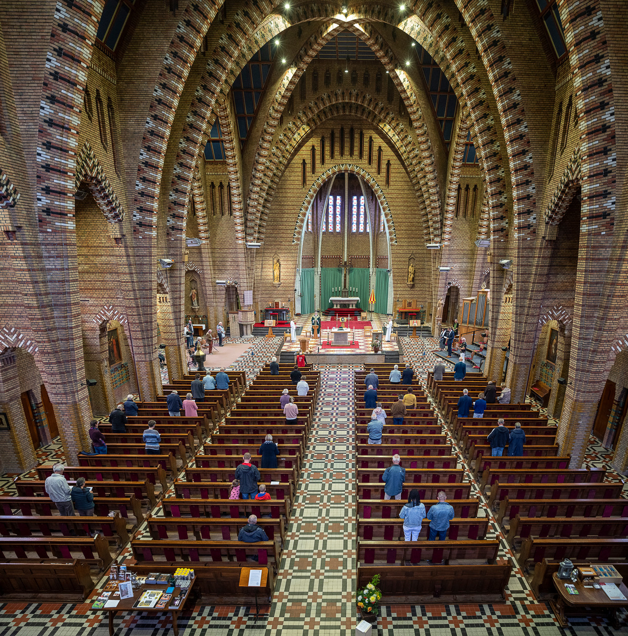Zondagdienst in de Sint Franciscusbasiliek in Bolsward met pastoor Arjen Bultsma. De 1,5-metermaatregel is duidelijk zichtbaar. Beeld Harry Cock / de Volkskrant