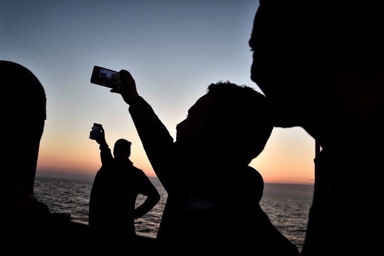 Migranten aan boord van de Aquarius nemen selfies tijdens zonsondergang op 30 mei 2018, voor de kust van Libië. Beeld AFP