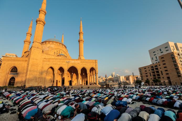 Moslims biddend bij een moskee, foto ter illustratie