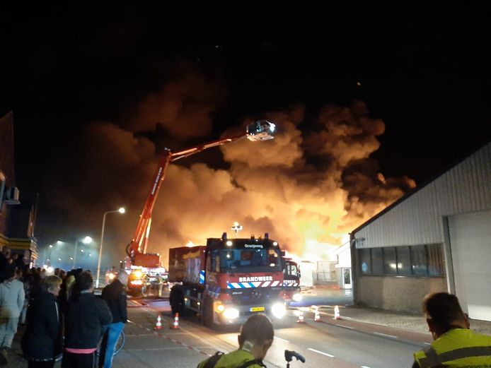 Brandweerlieden bestrijden het vuur in de keukenwinkel.