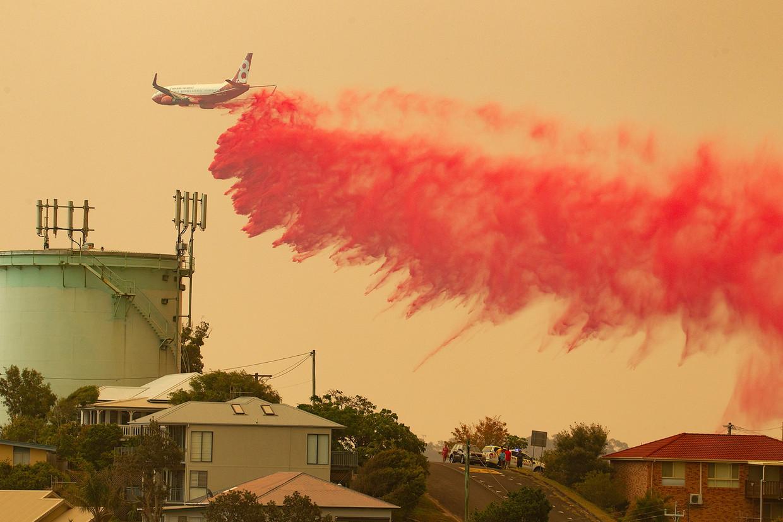 Een vliegtuig is bezig met het doven de branden boven Harrington, New South Wales.