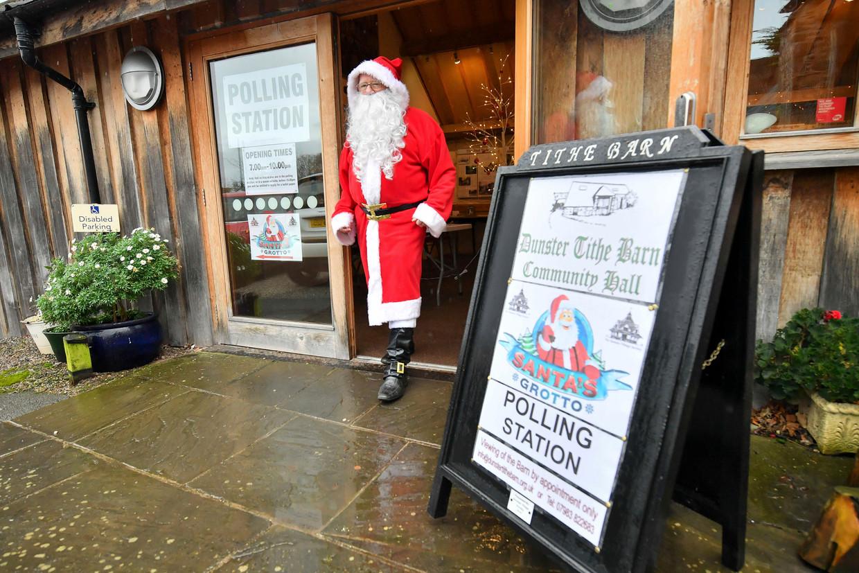 Een kerstman voor zijn kerstmannenhuisje, gebruikt als stemlokaal nabij Minehead, Somerset.