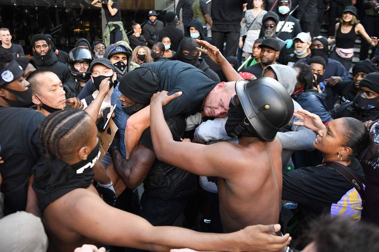 Een belaagde tegendemonstrant wordt door een aanhanger van Black Lives Matter bevrijd uit de boze menigte. Beeld AFP