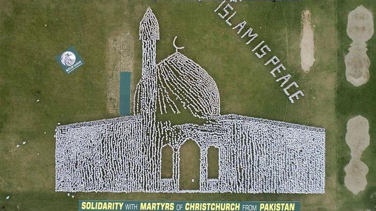 De gelovige Pakistanen beelden samen de moskee in Christchurch uit.