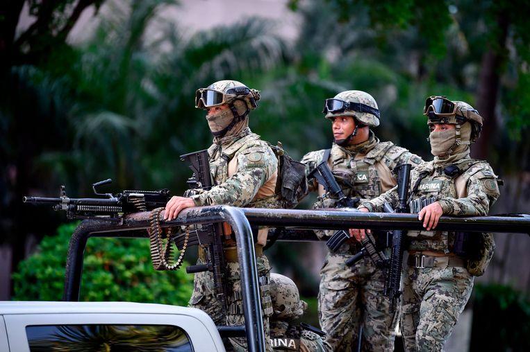 Soldaten bewaken een overheidsgebouw in de deelstaat Sinaloa na de arrestatie van de zoon van drugsbaas Joaquin Guzman, bekend als 'El Chapo'.  Beeld AFP