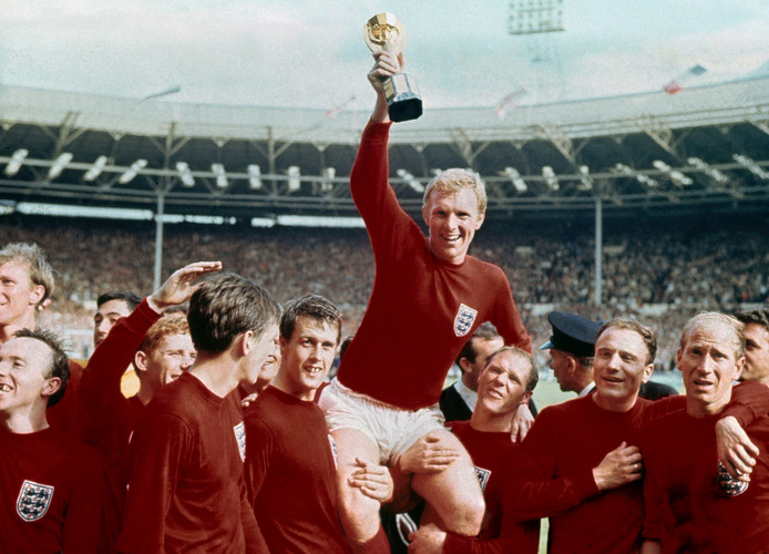 FILE - In this July 30, 1966 file photo, England's soccer captain Bobby Moore, center, is carried by teammates Geoff Hurst, center left, and Ray Wilson as he holds FIFA World Cup after England defeated Germany 4-2 in the final at London's Wembley Stadium. Ray Wilson, the left back for all six of England's games in its World Cup-winning campaign in 1966, has died. He was 83.