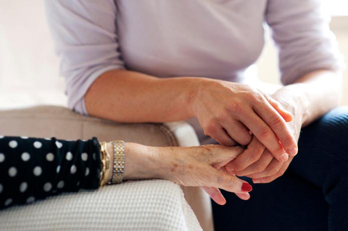 Een medewerkster biedt hulp aan een oudere dame