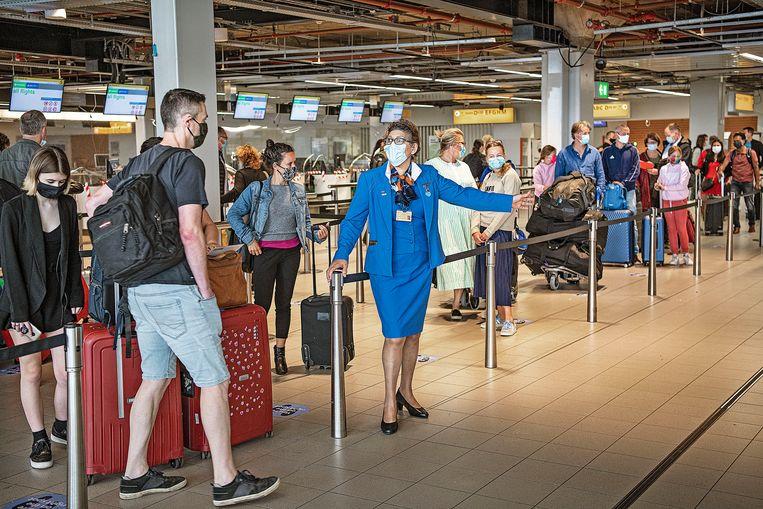 Wachtende reizigers bij een KLM-balie op 27 juli, de dag die normaal gesproken drukste van het zomerseizoen zou zijn geweest op Schiphol. Beeld Guus Dubbelman / de Volkskrant