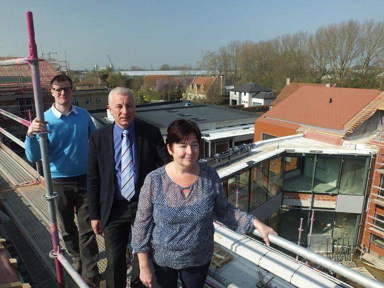 Zorgdirecteur Jan Beeusaert, directeur Ludo Timmermans en zorgcoördinator Chantal de Witte op het dak van een van de nieuwe woonhuizen. Achter hen ligt het lokaal dienstencentrum en daarvoor zie je een van de glazen gangen die de gebouwen met elkaar verbinden.