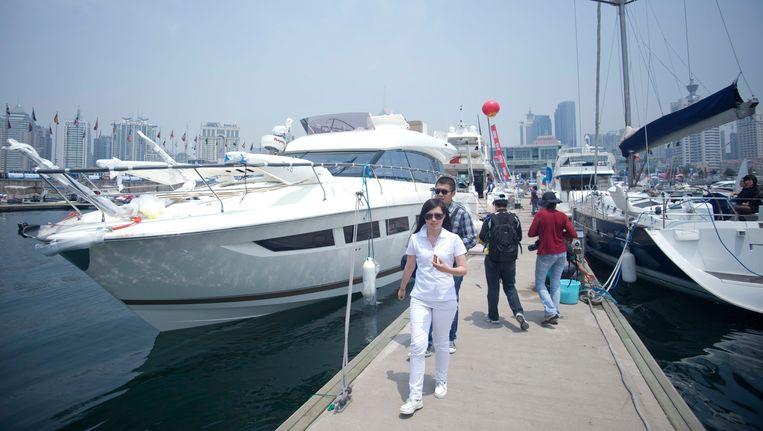 Bezoekers van een Chinese botenparade vol jachten en andere dure schepen in Qingdao. Beeld epa