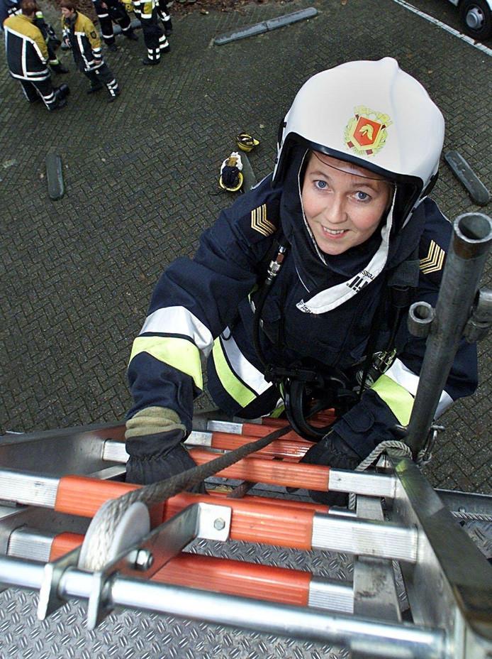 Een brandweervrouw beklimt een ladder