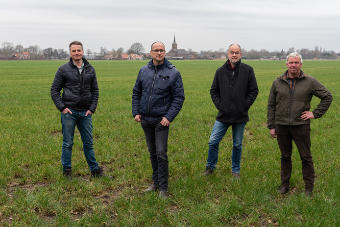 Van links naar rechts: Marco van de Veen, Marco van Meerveld, René Vaarkamp en Sjaak Malestein staan op de plek van een van de geplande windmolens. Zwartebroek ligt op de achtergrond.