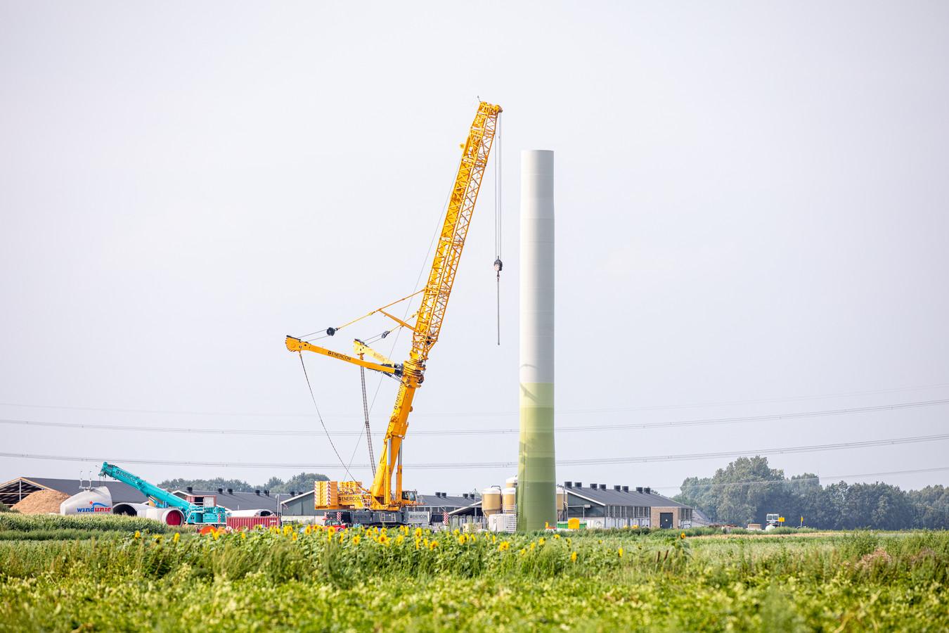 Met grote kranen worden de windmolens opgebouwd.