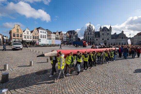Optocht op de Werelddag van Verzet tegen Armoede voor gelijke onderwijskansen. Leerlingen van De Luchtballon dragen een reuzengroot potlood.
