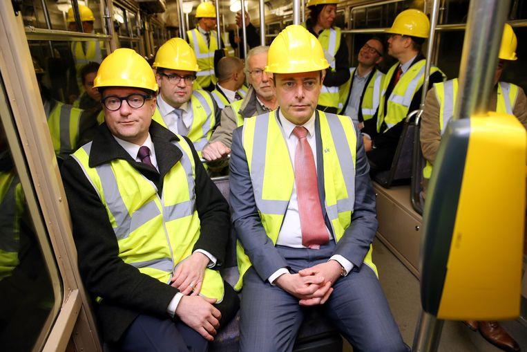 Ben Weyts en Bart De Wever in de tram. Zelfs in het rijtuig moesten ze een fluovest en een helm dragen.