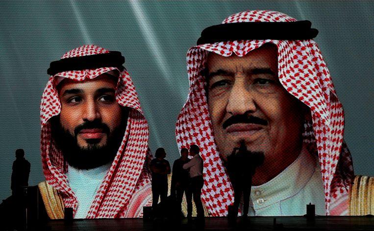 De Saoedische koning Salman (rechts) en zijn zoon en kroonprins Mohammed bin Salman op een reuzenafbeelding in Jeddah, Saoedi-Arabië. Beeld AP