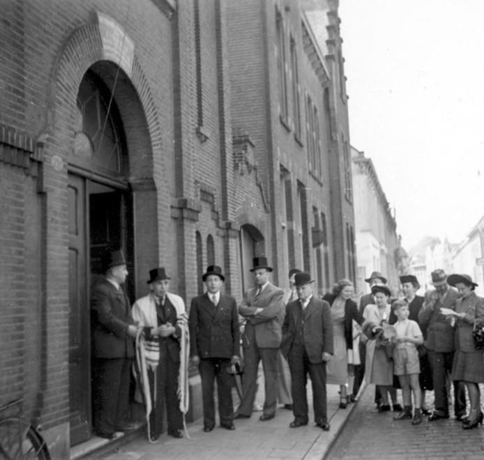 Leden van de joodse gemeente bij hun synagoge aan de Willem II-straat in het eerste naoorlogse jaar, 1945.