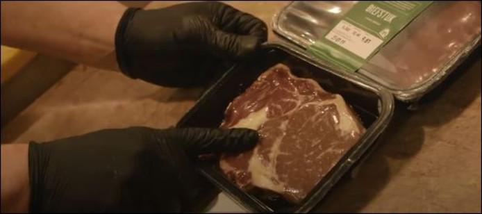 Slager van slagerij Hergo wijst naar de vetaders in het vlees.