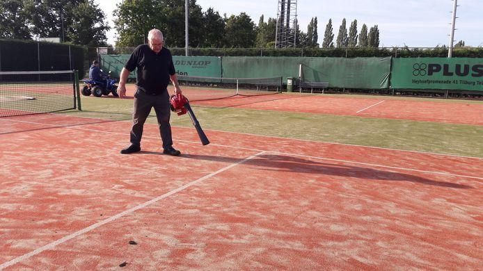 Bert Smulders blaast de roetdeeltjes van de tennisbanen.