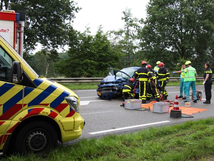 Hulpverleners buigen zich over het slachtoffer in Dongen. De auto zou zijn geramd door een vrachtwagen.
