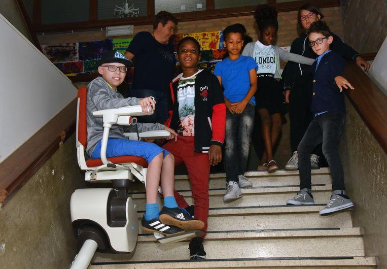 Boyd toont zijn schoolmakkers hoe hij met de traplift op- en afgaat.