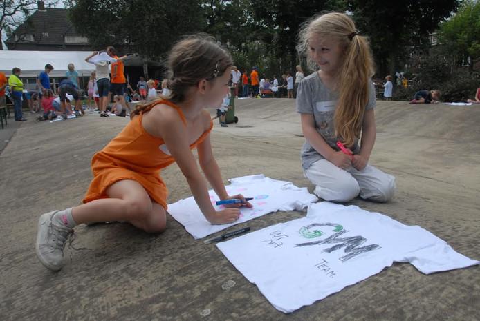 De kinderen zijn druk bezig met het versieren van de shirts