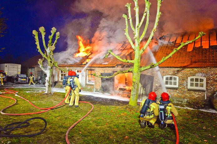 Brandweerlieden in actie bij een brand in een woonboerderij in Riethoven.