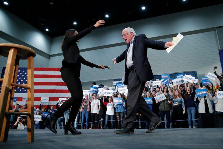 Bernie Sanders begroet tijdens zijn campagne in Iowa afgevaardigde Alexandria Ocasio-Cortez. Kandidaten die in de eerste ronde minder dan 15 procent halen, vallen af. Beeld AP