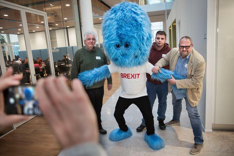 Ondernemers Alex Noorland, Martijn van Schaijk en Arjen Hes gaan op de foto met het brexit monster. Beeld Arie Kievit