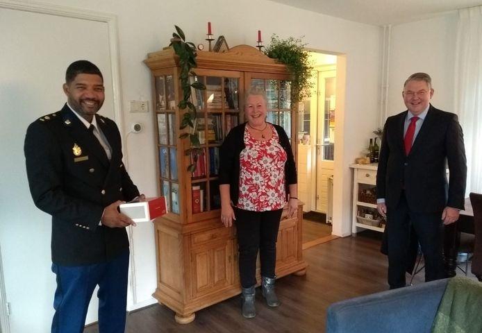 Olga Roffel wordt door politiechef Ramon Arnhem en burgemeester Hans Vroomen verrast met een lekker gebakje.