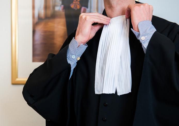 Een rechter schikt het befje om zijn toga.