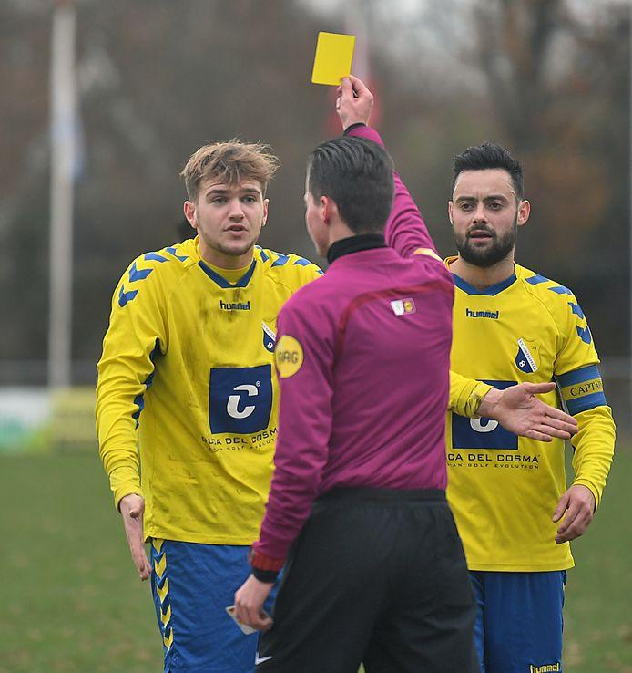 Scheidsrechter Felix toont Oostkapelle een gele kaart in het gestaakte duel met Nieuwenhoorn. Links staat Maarten Hazelaar en rechts Wouter Verduijn.