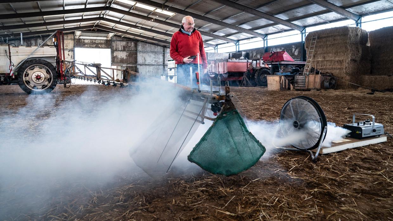 Akkerbouwer Daniel Edzes in zijn schuur, met zijn proefopstelling. Met een rookmachine bootst hij de wind na.