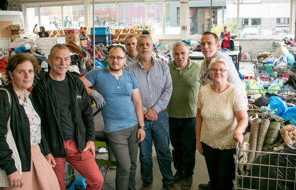 Den Azalee-voorzitter Sofie Heyrman en -directeur Peter Maris (links), met medewerkers in het sorteercentrum.