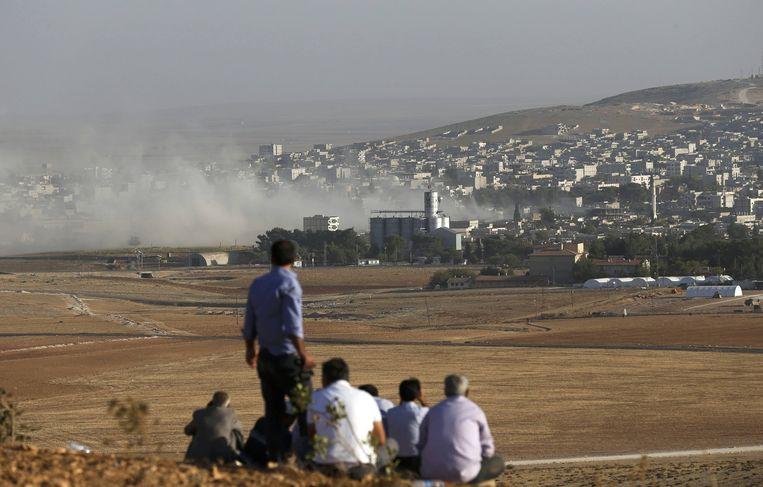 Turkse Koerden bekijken de gevechten in Kobani vanaf de grens. Beeld reuters