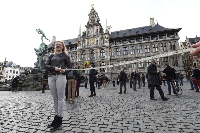 Freya Piryns houdt een vouwmeter vast om de verplichte afstand van 2 meter tussen manifestanten te bewaren.